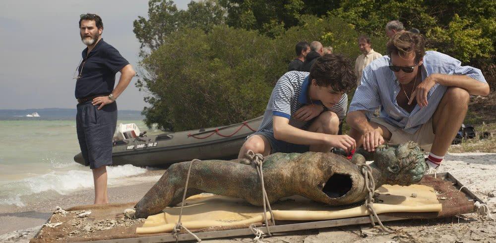 Elio (Timothée Chalamet) und Oliver (Armie Hammer) untersuchen einen archäologischen Fund am Strand, Vater (Michael Stuhlbarg) steht im Hintergrund in einem Szenenbild für Kritik Call Me by Your Name