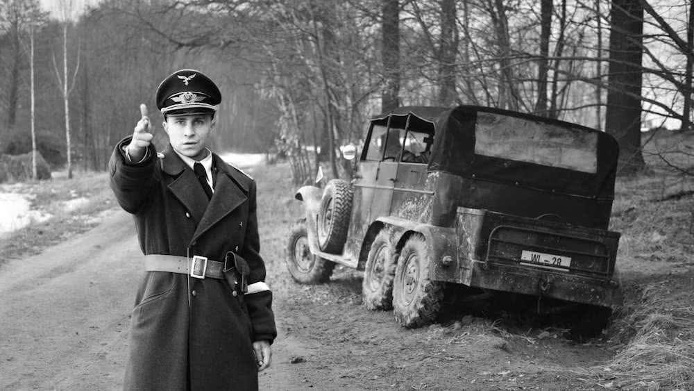 Max Hubacher als Willi Herold steht neben einem liegengebliebenen Geländewagen in einer SS-Uniform und zielt mit einer Fingerpistole in einem Szenenbild für Kritik Der Hauptmann