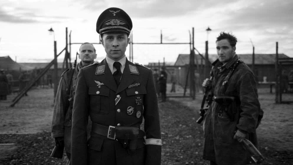 Max Hubacher, Milan Peschel und Frederick Lau stehen vor einem Gefangenenlager in einem Szenenbild für Kritik Der Hauptmann