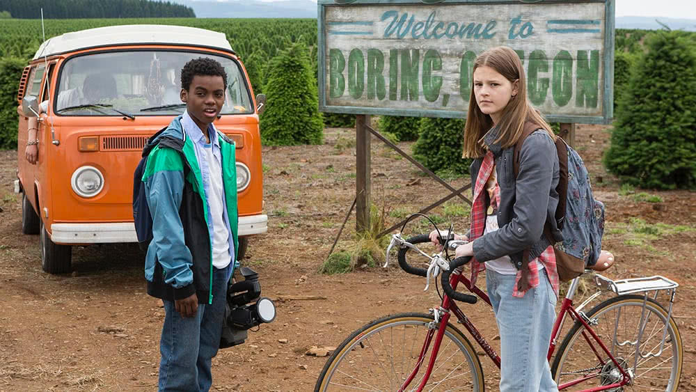 """Luke (Jahi Di'Allo Winston) und Kate (Peyton Kennedy) vor dem Ortsschild von """"Boring"""" in einem Szenenbild zu Kritik Everything Sucks Staffel 1"""
