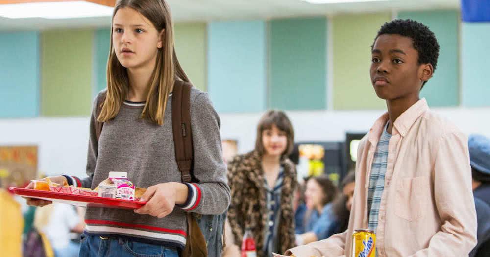 Luke (Jahi Di'Allo Winston) und Kate (Peyton Kennedy) stehen mit Tabletts in einer Schulkantine