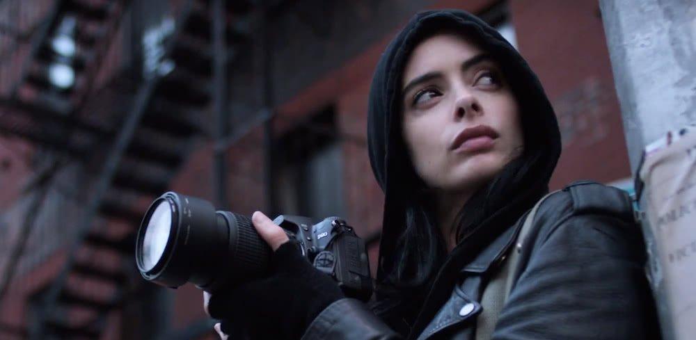 Krysten Ritter als Jessica Jones mit einem Fotoapparat auf einem Hausgerüst in einem Szenenbild für Kritik Jessica Jones Staffel 2