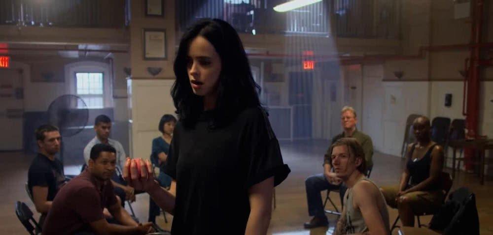 Jessica Jones steht am Rand einer Selbsthilfegruppe in einem Szenenbild für Kritik Jessica Jones Staffel 2