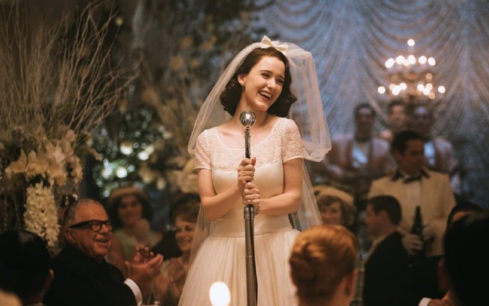 Rachel Brosnahan als Braut Midge hält auf einer Hochzeitsfeier eine Rede in einem Szenenbild für Kritik The Marvelous Mrs. Maisel Staffel 1