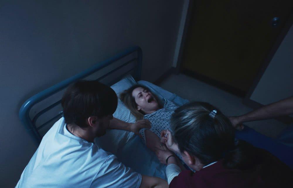 Claire Foy ist an ein Bett gefesselt in einem dunklen Raum in einem Szenenbild für Kritik Unsane