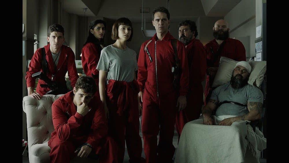 Der Haupt-Cast in roten Overalls in einem Szenenbild für Kritik Haus des Geldes