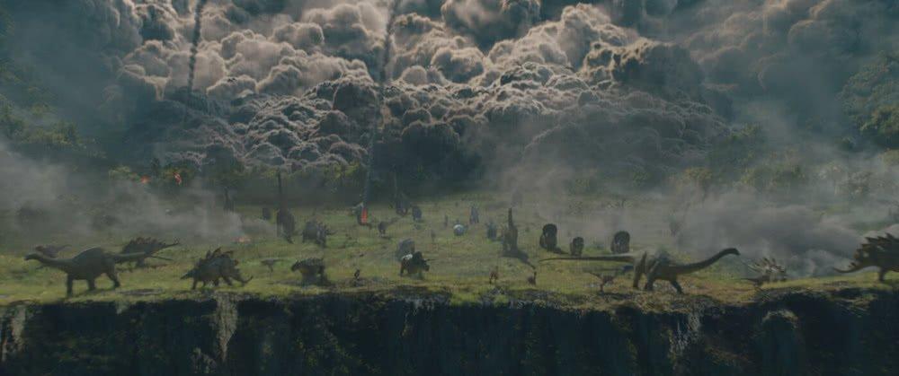 Szenenbild für Kritik Jurassic World Das gefallene Königreich mit einem ausbrechenden Vulkan und Dinos vor einer Klippe