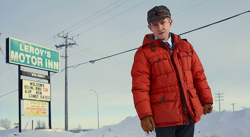 Martin Freeman in einer orangenen Daunenjacke vor dem verschneiten Schild eines Motels auf einem Plakat zu Fargo – Staffel 1