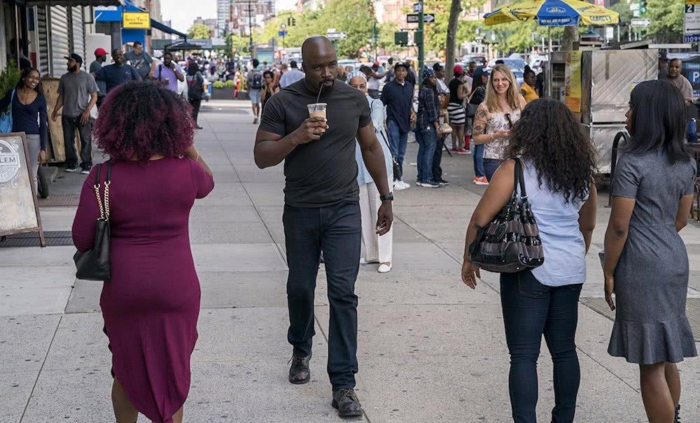 Luke Cage läuft durch die Straßen von Harlem in einem Szenenbild für Kritik Luke Cage Staffel 2