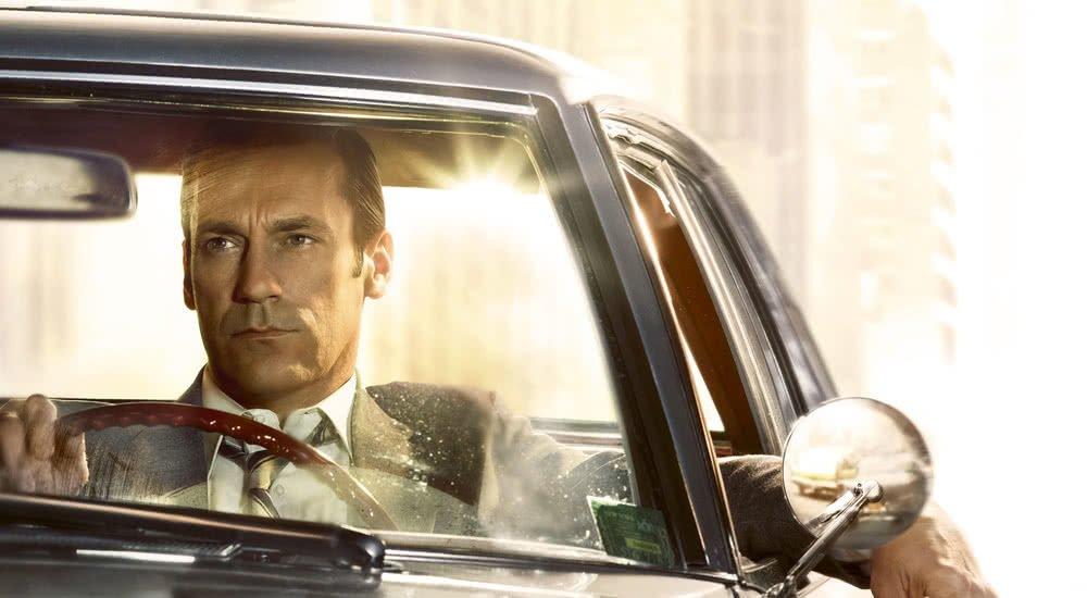 Jon Hamm als Don Draper sitzt in seinem Auto auf einem Plakat zu Mad Men Staffel 7