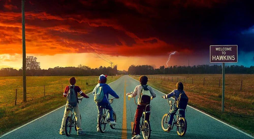 Die vier Hauptfiguren von Stranger Things auf ihren Fahrrad vor einer paranormal roten Wolke über einer Landstraße