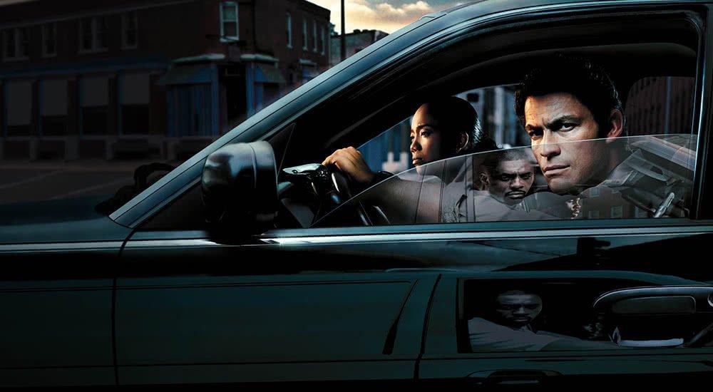 Dominic West als Detective James McNulty beschattet jemanden aus einem schwarzen Auto heraus in The Wire