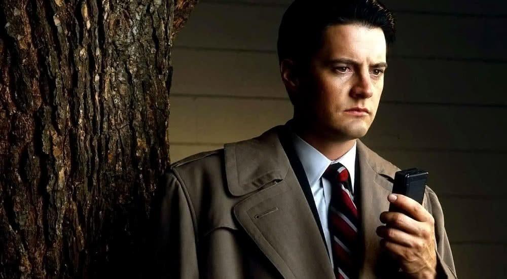 Kyle MacLachlan als Special Agent Dale Cooper nachdenklich mit seinem Diktiergerät in der Hand in Twin Peaks