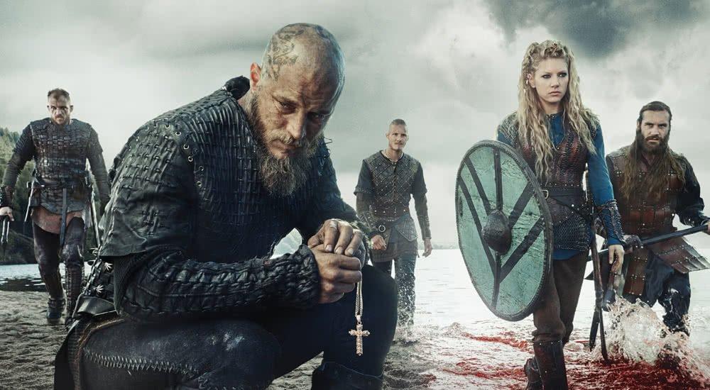 Travis Fimmel als Ragner Lothbrok und Katheryn Winnick als Lagertha sowie andere Hauptfiguren betreten schwer bewaffnet einen Strand der englischen Küste in Vikings Staffel 3