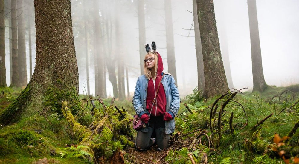 Madison Wolfe als Barbara kniet in einem Wald in I Kill Giants