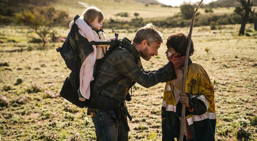 Martin Freeman als Andy mit Baby auf dem Rücken spricht zu der jungen Thoomi gespielt von Simone Landers in Cargo