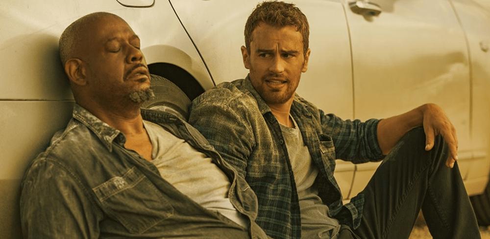 Theo James als Will und Forest Whitaker als Tom unterhalten sich am Boden sitzend vor einem Auto miteinander in How it Ends auf Netflix