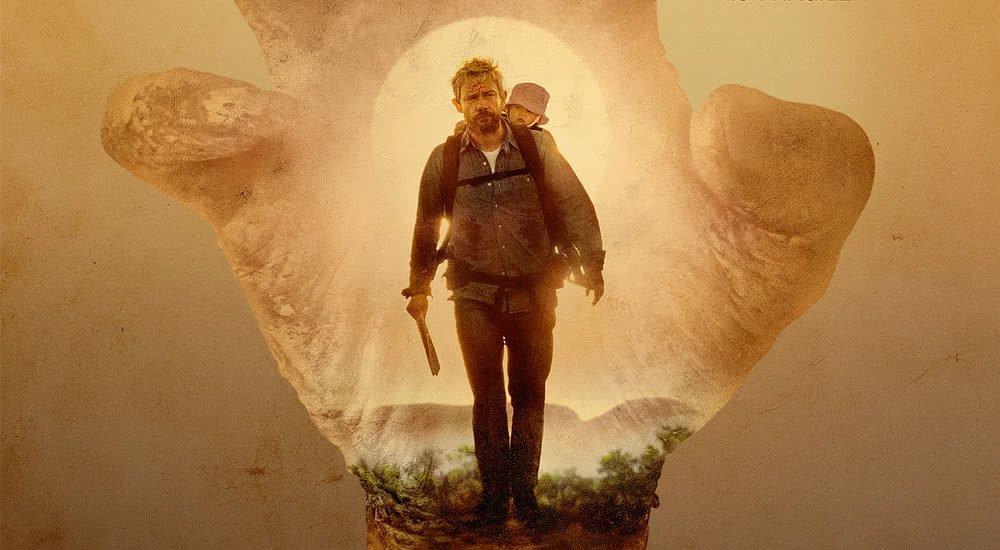 Martin Freeman als Andy mit einem Baby auf dem Rücken und Machete in der Hand im australischen Outback in Cargo auf Netflix.