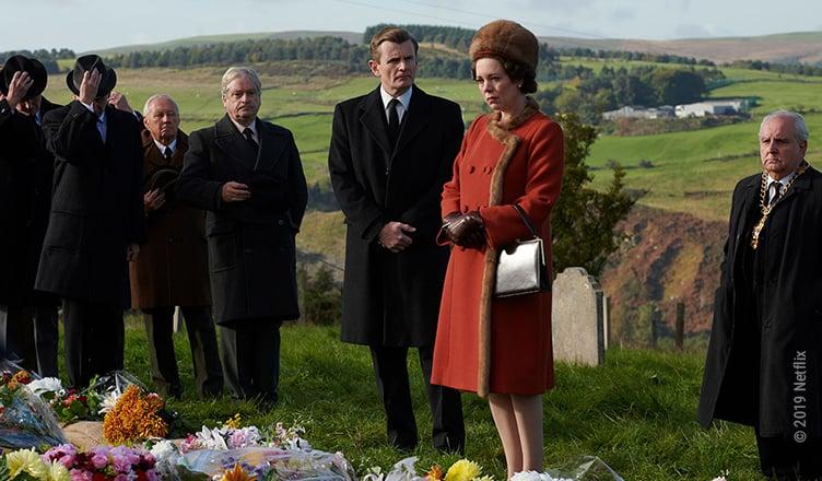 Königin Elizabeth II und viele Männer in schwarzer Kleidung stehen vor einem Grab mit Blumen