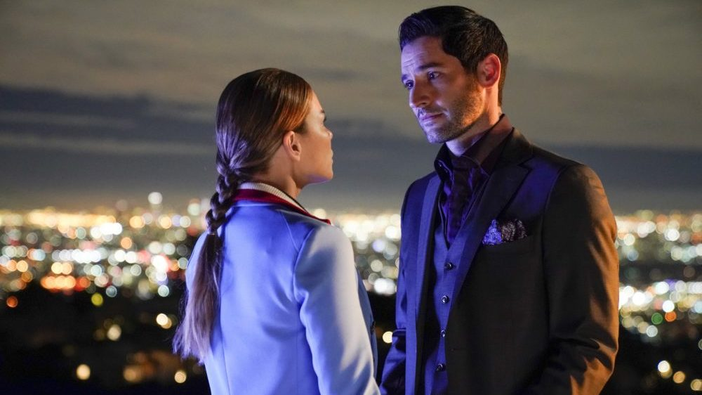 Lucifer (Tom Ellis) und Chloe (Lauren German) kommen sich Nahe vor einem beleuchteten Hintergrund.