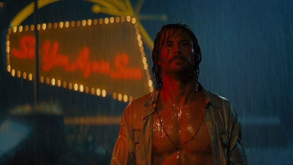 Chris Hemsworth steht vor einem Hotelschild im Regen in einem Szenenbild für Kritik Bad Times at the El Royale