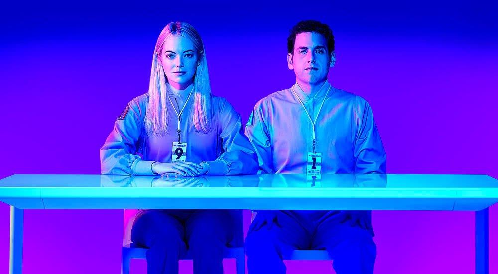 Die Hauptdarsteller von Maniac sitzen in purpurnem Licht an einem Tisch auf dem Plakat zu Maniac Staffel 1