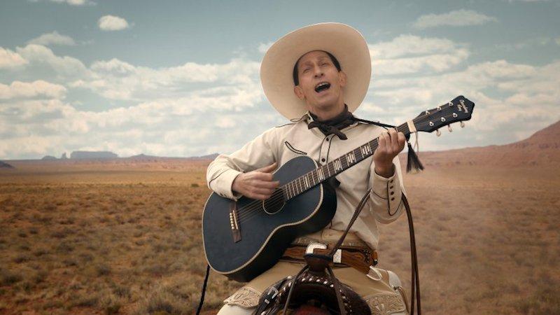 Tim Blake Nelson als Buster Scruggs mit einer Gitarre auf einem Pferd in der Prärie in einem Szenenbild aus The Ballad of Buster Scruggs Folge 1