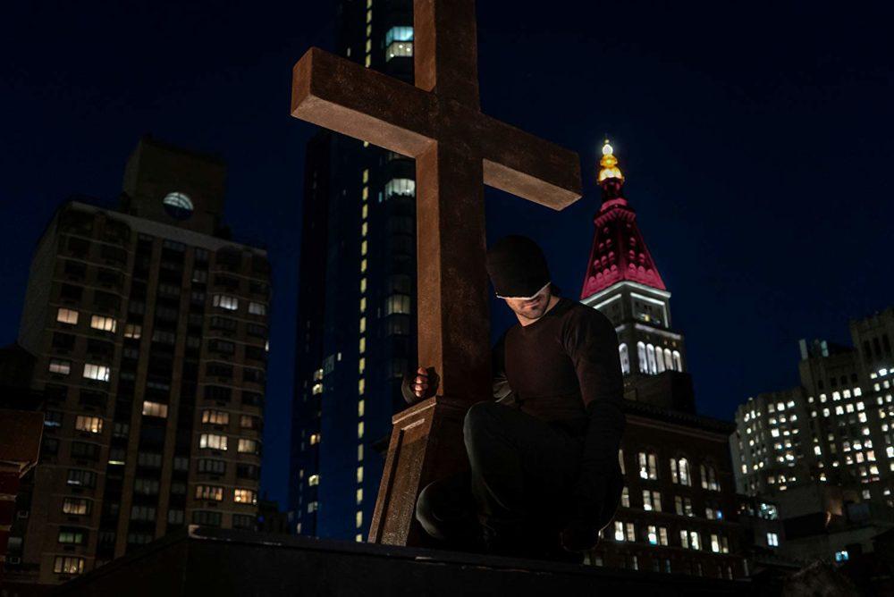 Daredevil (Charlie Cox) hält sich an einem Kreuz fest.