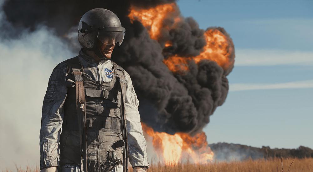 Ryan Gosling als Neil Armstrong vor brennendem Übungsflugzeug in Aufbruch zum Mond