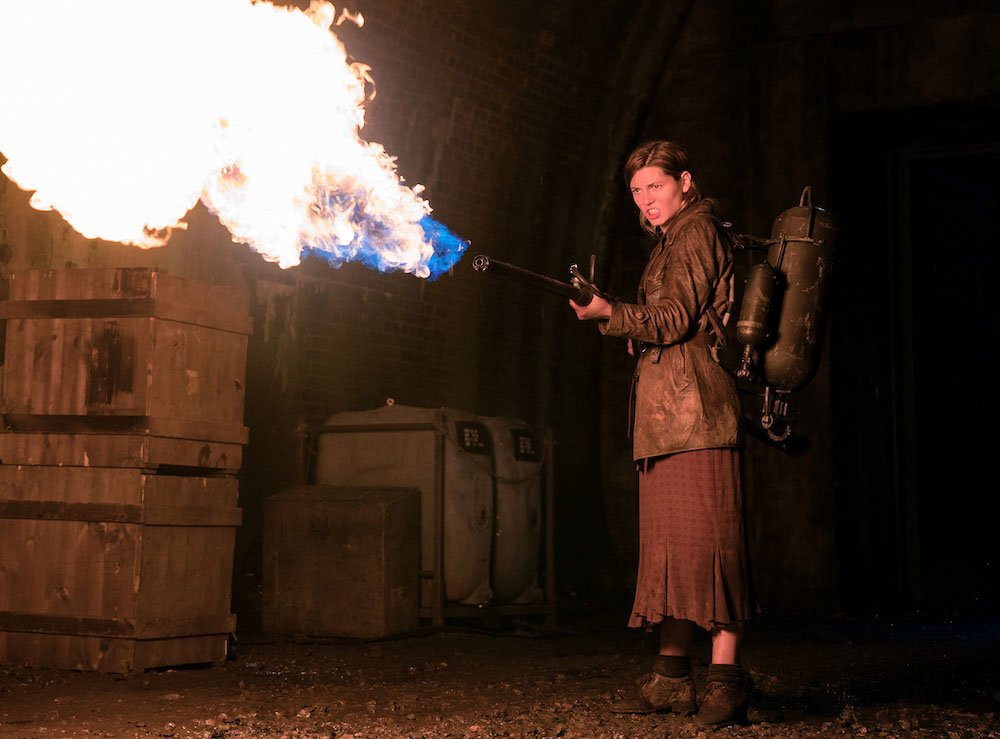 Frau mit einem Flammenwerfer in einem Tunnel in einem Szenenbild für Kritik Operation Overlord