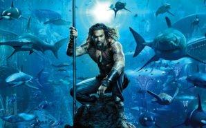 Aquaman (Jason Momoa) sitzt auf einem Felsen unter dem Meer, ausgerüstet mit einem Dreizack.