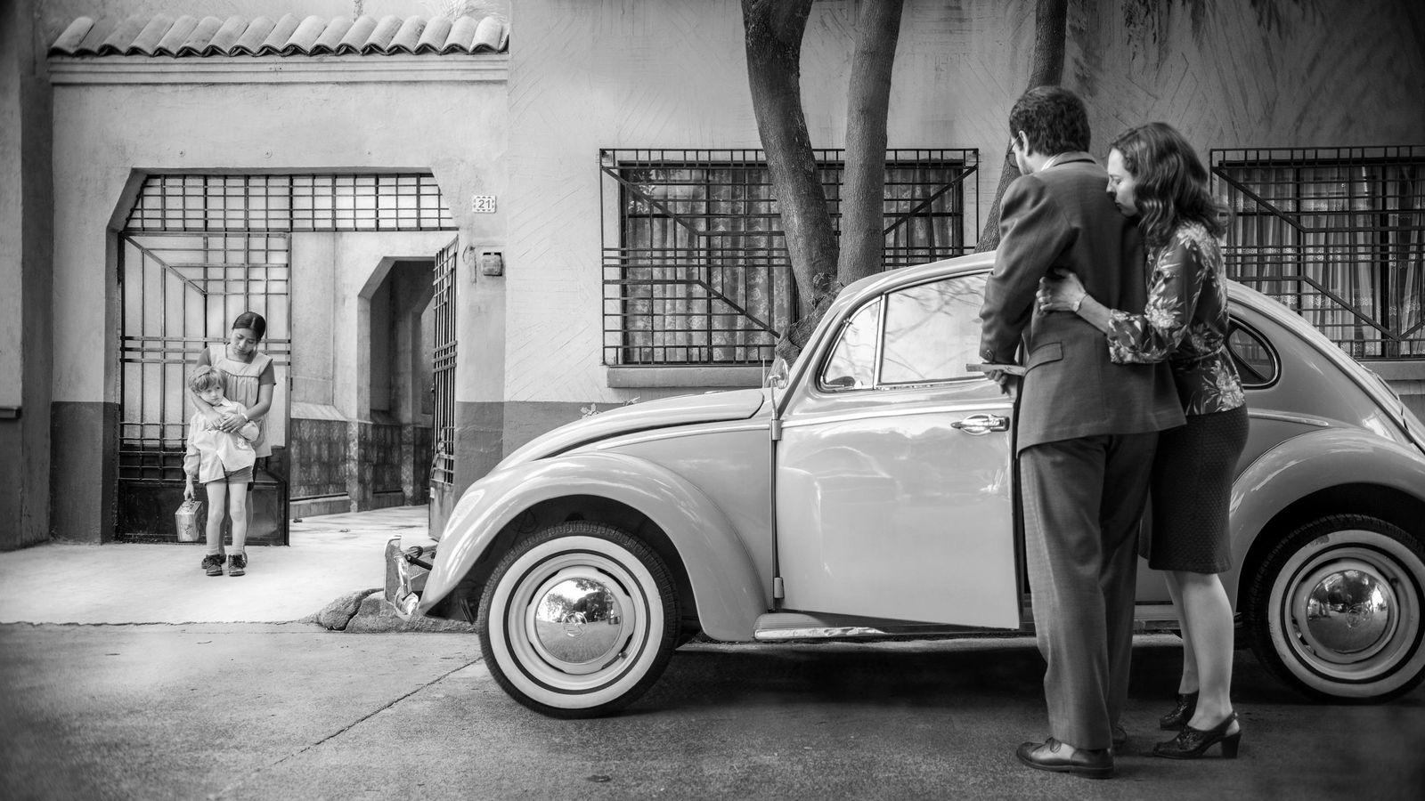 Szenenbild aus dem Film Roma von Alfonso Cuarón mit einem Käfer und einem Ehepaar vor einer Einfahrt