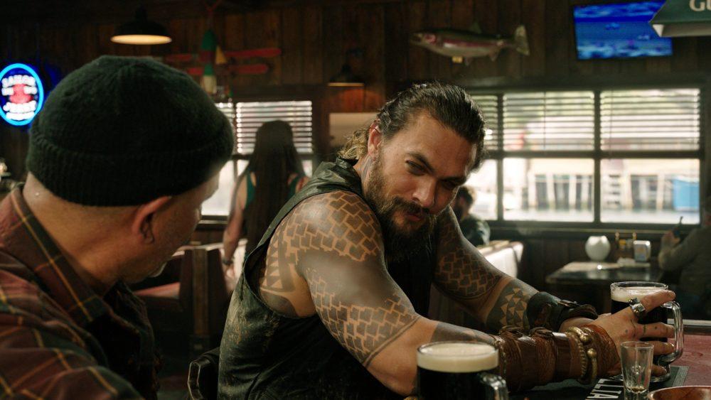 Arthur Curry (Jason Momoa) sitzt in einer Bar.