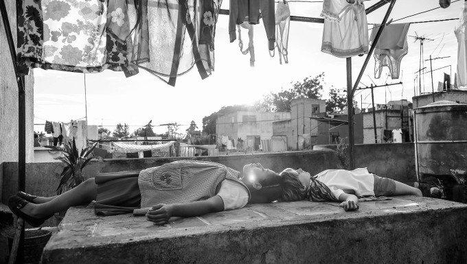 Cleo und Pepe liegen auf einem Dach in einem Szenenbild für Kritik Roma.