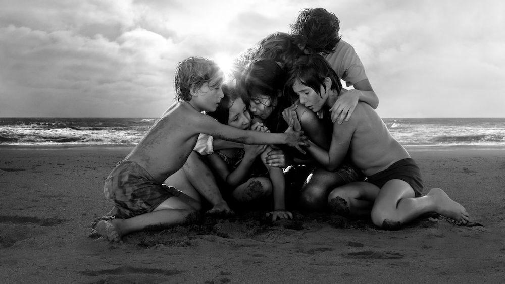 Titelbild für Kritik Roma mit einer Familie, die sich in den Armen liegt auf einem Strand