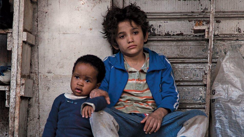 Zain Al Rafeea und Boluwatife Treasure Bankole sitzen auf der Straße in einem Szenenbild für Kritik Capernaum Stadt der Hoffnung