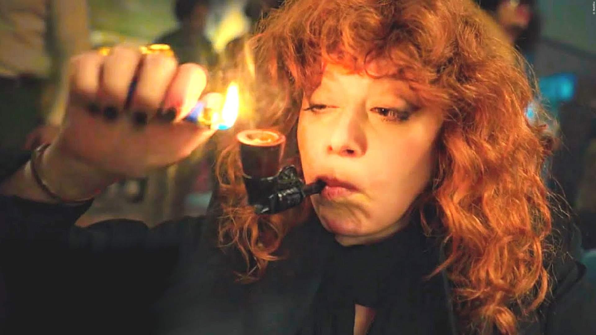 Natasha Lyonne zündet sich eine Pfeife an in einem Szenenbild für Kritik Matrjoschka Staffel 1
