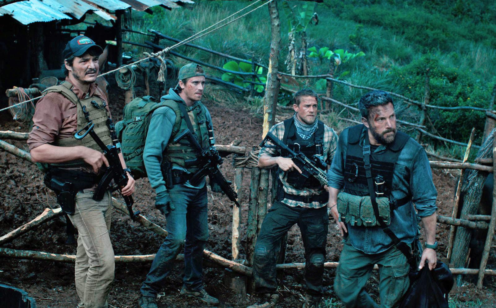 Oscar Isaac, Ben Affleck, Pedro Pascal und Garrett Hedlund im Dschungel in einem Szenenbild für Kritik Triple Frontier