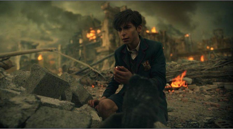 Nummer 5 (Aidan Gallagher) kniet vor einem postapokalyptischen Hintergrund.