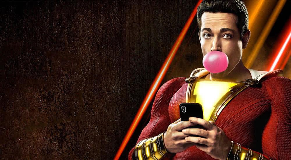 Shazam in Superheldenanzug mit Kaugummi-Blase und Smartphone