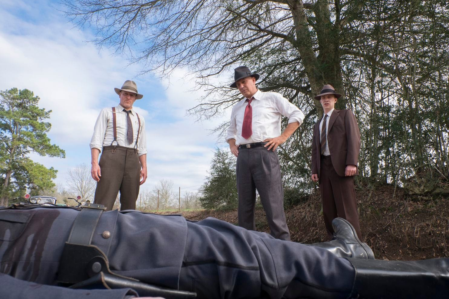 Woody Harrelson und Kevin Costner als Texas Ranger stehen auf der Leiche eines Polizisten auf einer Straße.