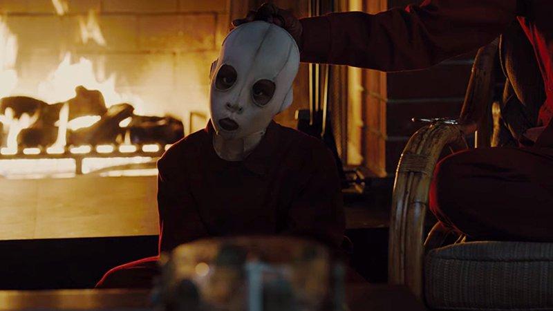 Eine Person mit Maske sitzt vor einem Kaminfeuer in einem Bild für Kritik Wir