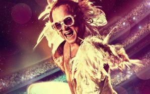 Taron Egerton als Elton John in einem weißen Anzug auf der Bühne in einem Szenenbild für Kritik Rocketman