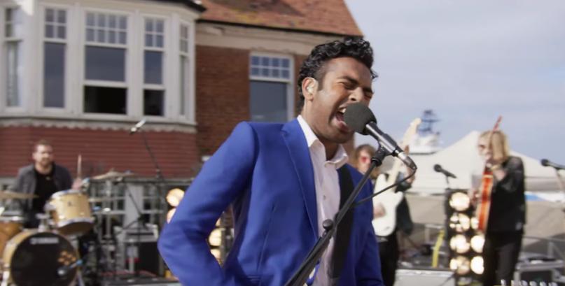 Himesh Patel mit Gitarre auf einer Bühne in einem Szenenbild für Kritik Yesterday