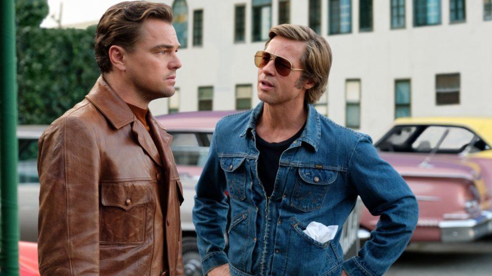 Rick Dalton (Leonardo DiCaprio) und Cliff Booth (Brad Pitt) vor parkenden Autos.