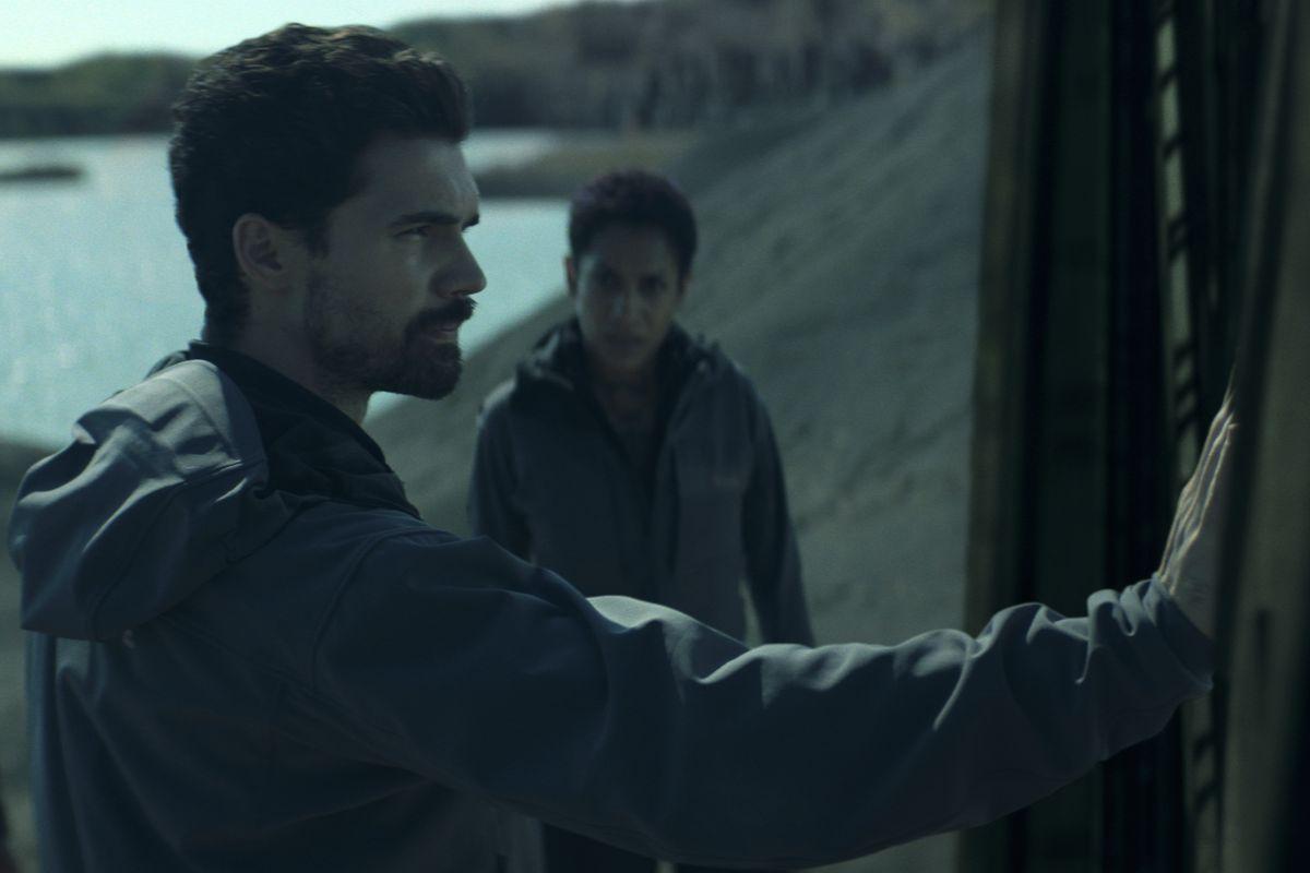 Steven Strait und Dominique Tipper vor einem Tor auf Ilus in einem Szenenbild für The Expanse Staffel 4