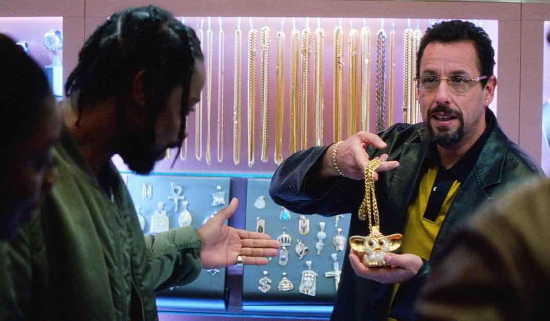 Adam Sandler hält ein Schmuckstück in der Hand in einem Szenenbild aus Netflix Original Der schwarze Diamant