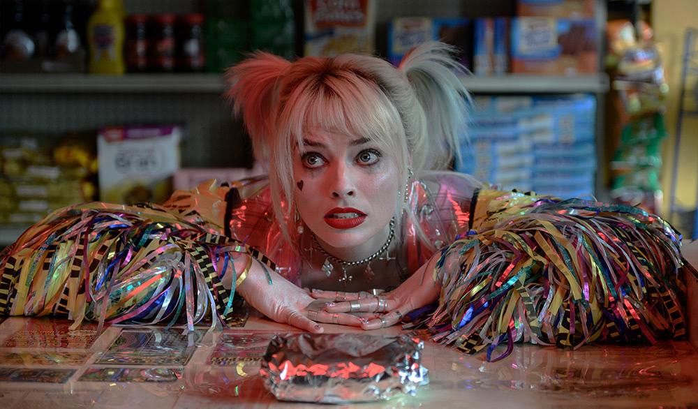 Harley Quinn (Margot Robbie) lehnt sich an einen Tisch