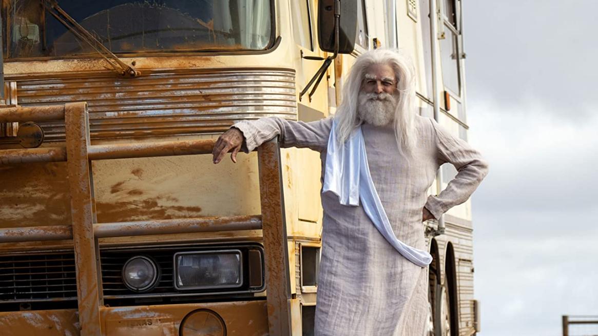 (Mark Harelik) Gott steht vor seinem Wohnwagen in der Wüste.