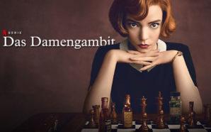 Junge, rothaarige Frau sitzt an einem Tisch mit einem Schachbrett an Spielfiguren und Schnapsfläschchen und schaut direkt in die Kamera